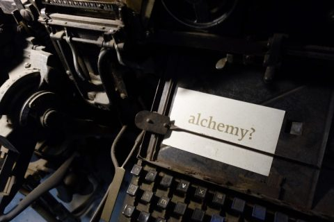 linotype machine with a card with the word alchemy printed on it
