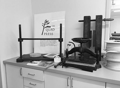 Sewing frames and book presses flank a poster on the newly minted MacOdrum Library imprint, The Quad Press