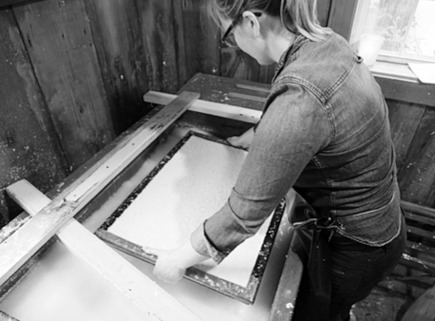 Vatwoman Brynn Dooley at Crown Mills removes the mould and deckle from the vat and provides the requisite shake to 'set' the fibres.
